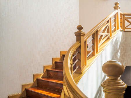 Wooden stairway with handrail and stainless banister, white wall, modern home interior.