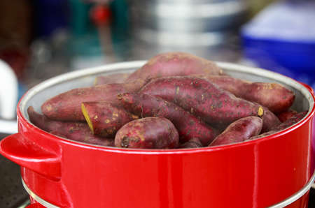 Sweet hot boil potatoes in the red pot ready to serve