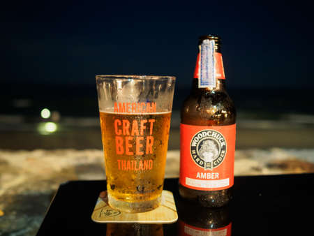 HuaHin, Thailand - April 9, 2017: Bottle of Woodchuck Amber beer and glass of American Craft Beer on the table at HuaHin Beach during night time. Editorial