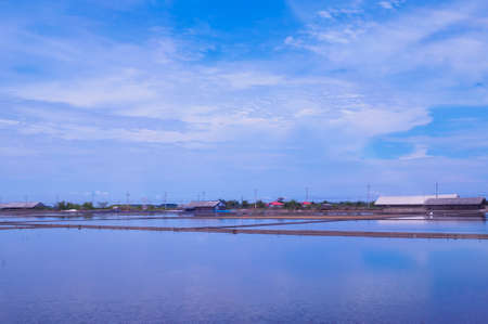 Salt field with shanty in panorama view, with blue ocean color background. Feeling of being immense and lonely.
