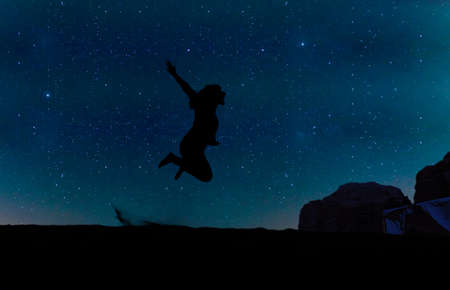Silhouette of young woman jumping over sand hill, beneath the stars, Milky Way and a lot of stars over the mountain at Wadi Rum desert.  Concept for happiness, traveling and freedom.