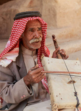 Little Petra, Jordan – June 20, 2017: Old Bedouin man or Arab man in traditional outfit, playing his musical instrument at the doorway of Little Petra.