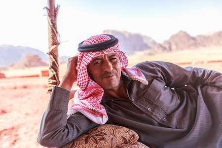 Wadi Rum, Jordan – June 20, 2017: Bedouin man or Arab man in traditional outfit, lying down on the couch, desert background. Editorial