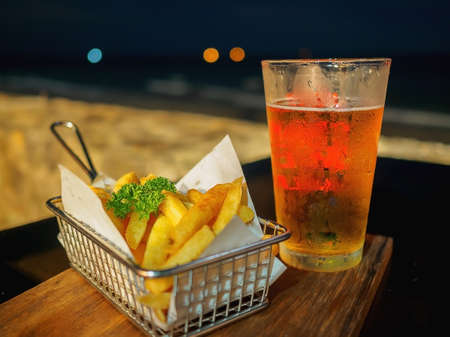 Glass of beer and French fried on the table at the beach during night time.