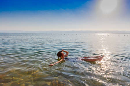 Mädchen, das auf Oberfläche des Toten Meers, Jordanien, schwimmt, genießen ihre Ferien während der Sonnenuntergangzeit im Sommer. Konzept für Urlaub, Reisen, Lifestyle und Wellness. Standard-Bild