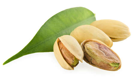 Pistachios and a green leaf on a white background Stock Photo