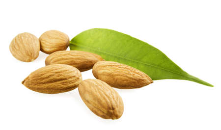 Almonds and a green leaf on a white background Stock Photo