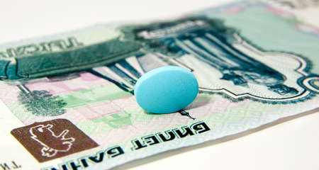 Big blue medicine tablet lies on money Stock Photo