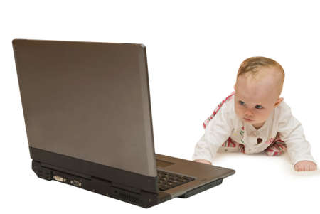 Baby stand on all fours and looks on computer