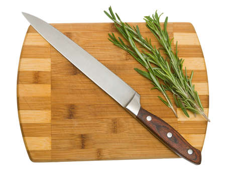rosemary on the cutting board with the knife lie obliquely