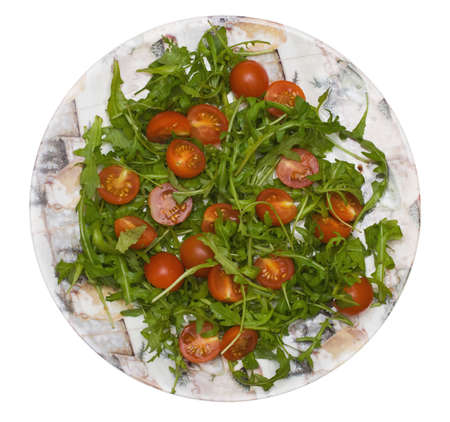 Salad with tomato and rucola on white background, view on top