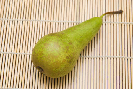 Green pear on bamboo substrate
