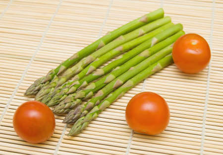 Aspargus stems and tamatos on bamboo substrate  Stock Photo