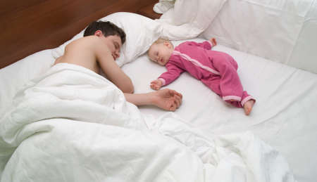 Dad and child are sleep on bed