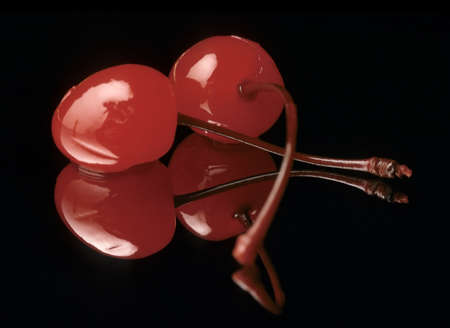maraschino: Maraschino cherries reflecting on black