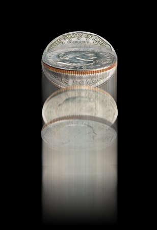 Coin flip on black Фото со стока