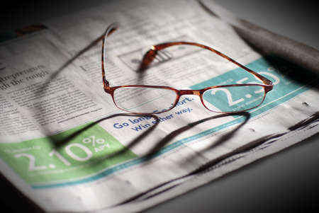 glasses and business section of newspaper