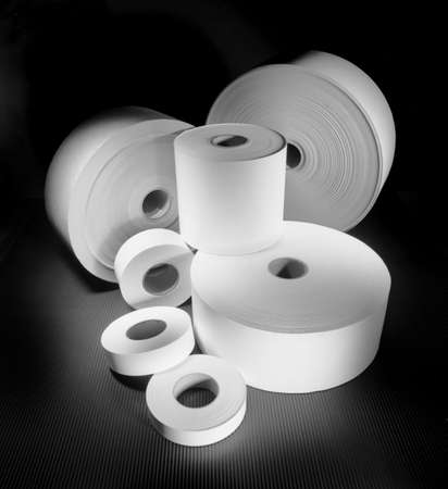 rolls of different sized paper on dark background in balck and white 版權商用圖片