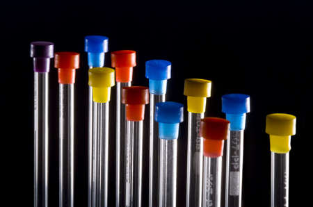 test tubes with multicolored tops back lit on black