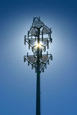 Cell tower back lit by sun on a clear blue sky