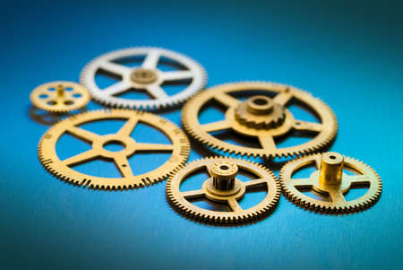 Various gears almost meshing on cyan and blue background with limited DOF