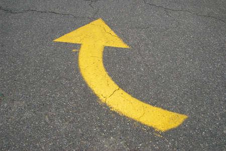 Yellow painted arrow on asphalt street going right