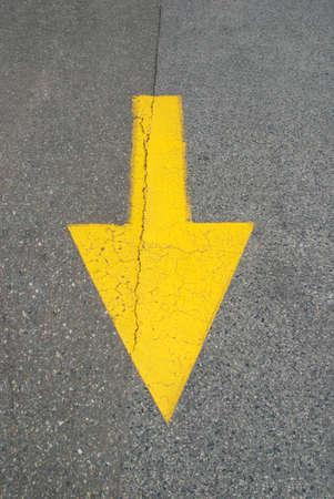 アスファルトの道路に黄色の塗られた矢印 写真素材