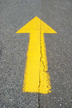 Yellow painted arrow on asphalt street Stock Photo - 7260602