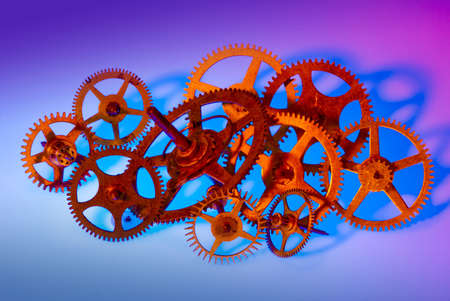 Various sized clock gears bunched together and lit with colored spot lights