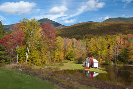 Scenic fall view of New Hampshire water mill on pond