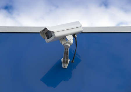 Security surveillance camera on the side of an industrial building photo