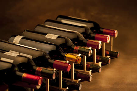 Red wine bottles stacked in rack on warm background photo