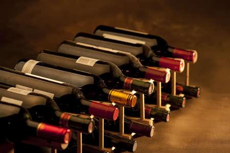 Rode wijn flessen gestapeld in rack op warme achtergrond Stockfoto