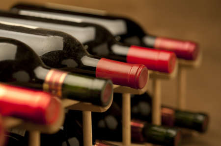 Red wine bottles stacked in rack on warm background