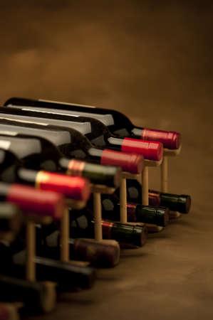Rode wijn flessen gestapeld in rek op een warme achtergrond, verticale