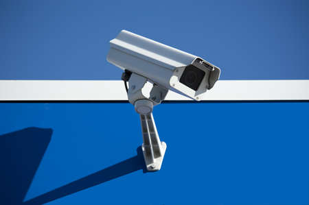 security technology: Security surveillance camera on the side of an industrial building