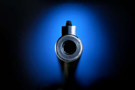 barrel pistol: Gun barrel on blue pointing straight on Stock Photo