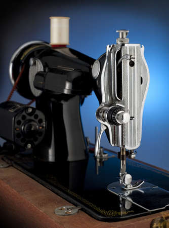 machine: Antique sewing machine back lit by a blue spot light