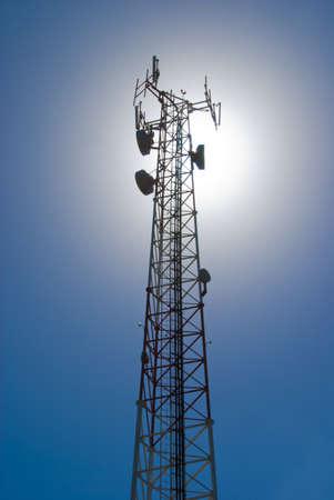 通信: 太陽に照らされて戻ってセル タワーやラジオ アンテナ 写真素材