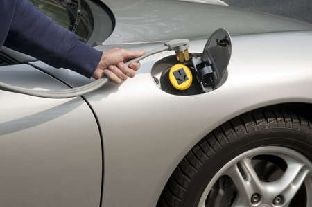 Silver electric car home refueling with a 220 volt line photo