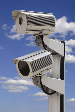 Two security surveillance cameras on blue sky photo