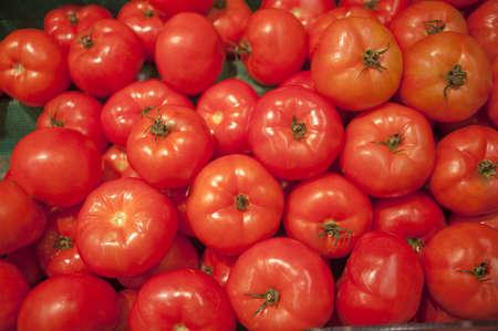 bunched: Bel pomodoro maturo raggruppato insieme su una bancarella del mercato