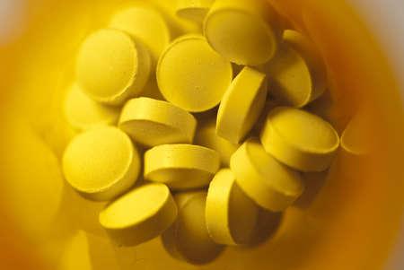 pilule: Vista de macro de p�ldoras de un disparo en una botella de medicina amarillo