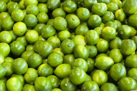bunched: Fresh green limes bunched together at a farm stand Stock Photo