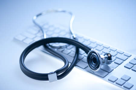 Medical stethoscope on a  computer keyboard in blue, closeup  Stock Photo - 10133715