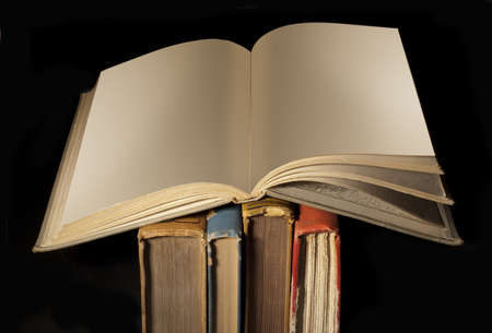 book spines: Blank open book on top of old worn spines on black Stock Photo