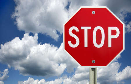 Stop sign against a dark cloudy sky with a clipping path for sign