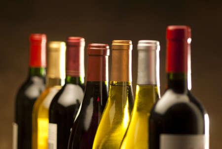 uvas vino: Botellas de vino en una fila con limitada profundidad de campo