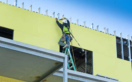 Construction worker screwing outdoor sheet rock into new building Stock Photo