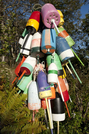 Multi colored lobster buoys hanging from a pole in small Maine fishing village photo